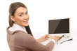 A smiling woman working with a laptop and looking back