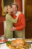 Woman kissing husband on cheek by turkey on dinner table, portrait of man