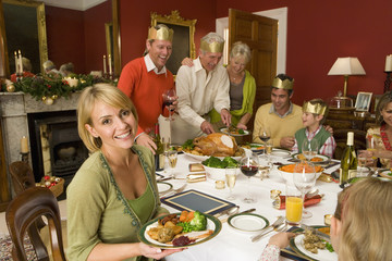Family having Christmas dinner, portrait of woman smiling
