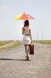 Young fashion girl with umbrella and suitcase at spring outdoor.