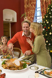 Family having Christmas dinner, woman kissing husband cutting turkey