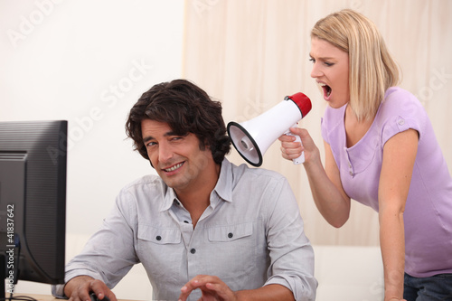 a man doing computer and a woman yelling on him with a megaphone