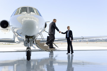 Man boarding aeroplane on runway shaking hands with woman