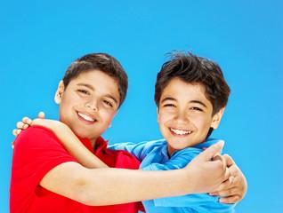 Happy cute boys over blue sky