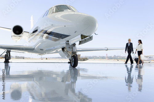Two women walking towards aeroplane on runway