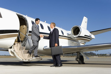 Businessman boarding aeroplane on runway, shaking hands with colleague