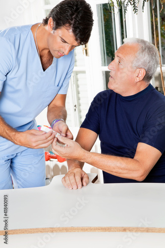 Male Nurse Checking Sugar Level Of Senior Man