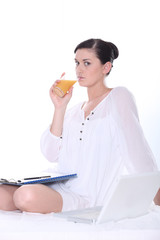 Woman drinking juice with a laptop and clipboard