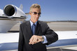 Businessman in sunglasses by aeroplane on runway, looking at wrist watch