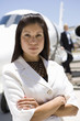 Businesswoman with arms crossed by aeroplane on runway, portrait