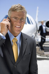 Businessman in glasses with hand on earpiece by aeroplane on runway, smiling, portrait
