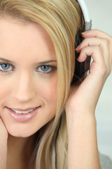Young blond woman listening to music with headphones