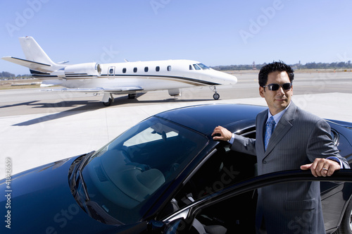 Businessman in sunglasses by open door of car on runway by aeroplane, elevated view