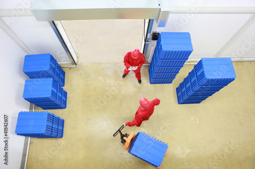 goods delivery - two workers in small warehouse