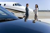 Two businesswomen by car and aeroplane on runway, portrait, side view