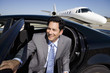 Businessman getting out of car on runway by aeroplane, smiling, portrait