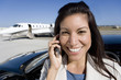 Businesswoman using mobile phone by car on runway by aeroplane, smiling, portrait, close-up