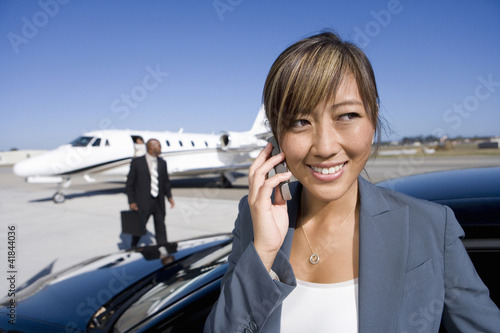 Businesswoman using mobile phone by car on runway by aeroplane, smiling, close-up