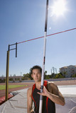 Young male pole vault athlete with pole by bar, portrait (sun flare)