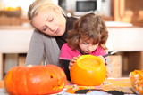 Mother and daughter preparing pumpkin in kitchen