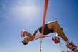 Young male athlete jumping over bar, low angle view (lens flare)