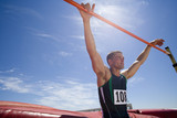 Young male athlete with hands on bar, low angle view (lens flare)