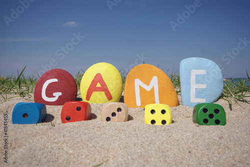 dices game concept with colourful stones on the sand