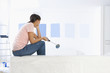 Woman sitting on sofa and examining blue paint samples on living room wall