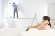 Woman on sofa watching man paint living room wall on wood plank