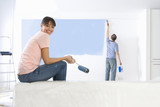 Woman holding paint roller and smiling as man paints living room wall in background