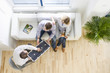 Salesman showing solar panel to couple sitting on sofa in living room