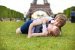 Laughing couple lying on the grass near the Eiffel Tower