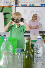 Teacher watching student use recyclable tin cans for binoculars