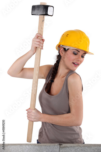 Tradeswoman using a mallet to hit stones