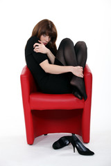 woman wearing stockings huddled in armchair