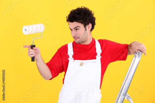 Man with paint roller and ladder