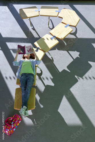 Student laying on row of school desks formed into a question mark symbol studying