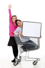 Children with a shopping trolley and blank board