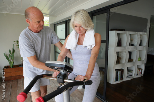 Man helping his wife use an exercise machine