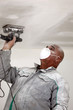 Man wearing mask whilst sanding ceiling