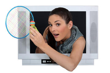 Woman with badminton racquet escaping from television