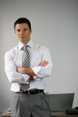 Serious businessman man by his desk arms folded