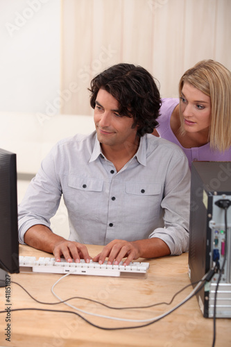 Man helping colleagues with computer issue
