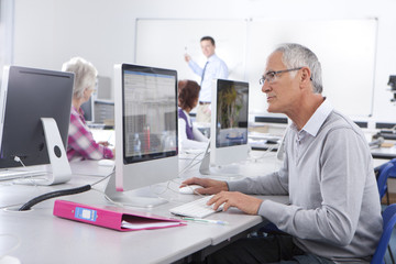 Serious adult student studying in college evening class computer lab