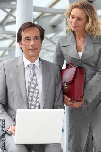 Man using a laptop computer accompanied by a woman