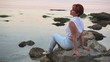 The harmonous woman sits on the seashore in the evening
