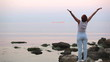 The woman on the seashore подымает hands up also stretches