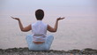 The meditating woman on the sea coast