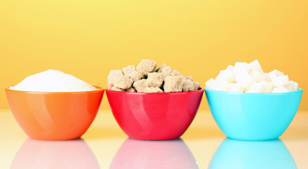 Colorful bowls with different types of sugar