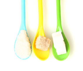 Bright colorful spoons with different types of sugar